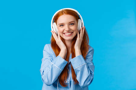 Waist-up shot cheerful pretty foxy caucasian girl listening music in large headphones, smiling pleased, checking-out friends single, wearing nightwear, standing blue background delighted