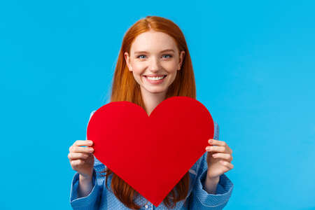 Happy, cheerful and lovely, tender caucasian woman holding big red heart valentines card and smiling, giving her love and care, congratulate boyfriend with their romantic date, blue background