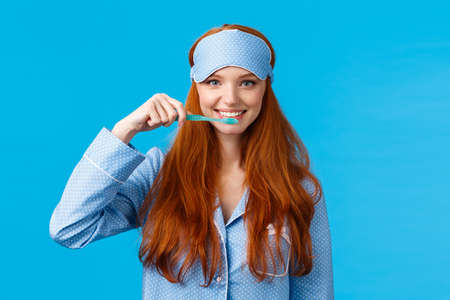 Habits, hygiene and lifestyle concept. Cute feminine redhead european woman in nightwear, sleep mask smiling and brushing teeth with toothbrush, standing blue background
