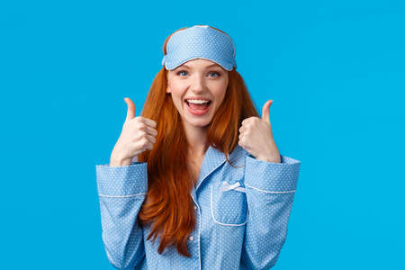Waist-up portrait delighted, fully satisfied cute redhead girl in sleeping clothes, nightwear and sleep mask, showing thumbs-up in approval, like or agree gesture, standing blue background amused Фото со стока