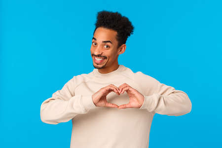 I love you. Cheerful and cute enthusiastic african-american smiling boyfriend making heart hands gesture near chest and grinning camera, make confession on valentines day, blue background Stok Fotoğraf