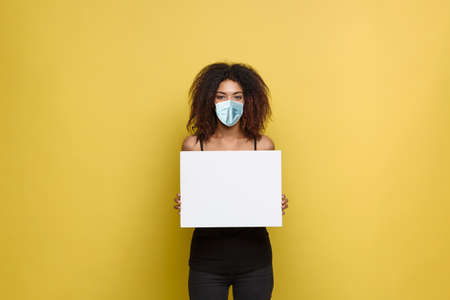 Covid19 Concept - Close up Portrait young beautiful attractive African American with face mask showing plain white blank sign.