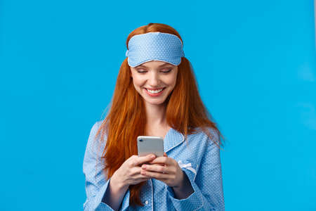 Mobile addication, technology and beauty concept. Cheerful girl waking up and grab phone, checking messages, scrolling news feed on smartphone wearing nightwear, sleep mask, smiling