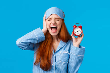 Upset and distressed screaming redhead lovely girl feeling bothered and depressed, holding red alarm clock and shouting with closed eyes and uneasy face, being late, hate wake-up early Фото со стока