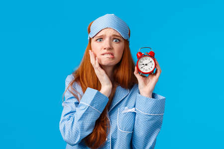 Concerned, nervous and panicking young redhead woman feel embarrassed and bothered, anxiously biting lip frowning touch face worried, showing red alarm clock, blue background Фото со стока