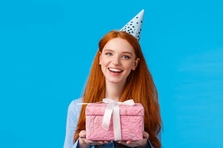 Time for present. Cheerful redhead teenage, college girl celebrating her birthday, holding cute pink wrapped gift and wearing b-day hat, joyfully smiling standing blue background