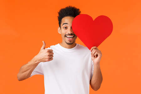 Love good. Charismatic african-american smiling man in white t-shirt, holding romantic valentines card and showing thumb-up, found true love in dating app, celebrate with boyfriend, orange background