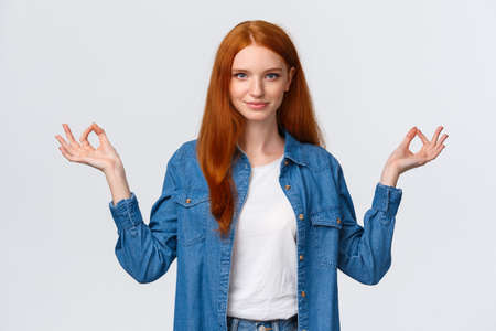 Waist-up portrait confident and relieved, patient good-looking redhead woman calm down daily yoga practice with app, hold hands sideways zen gesture in lotus pose, look assertive camera