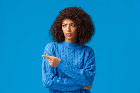 What a heck. Displeased and reluctant african-american bothered woman with afro haircut, pointing looking left with disapproval, express condemn or scorn, standing unsatisfied blue background Stock Photo