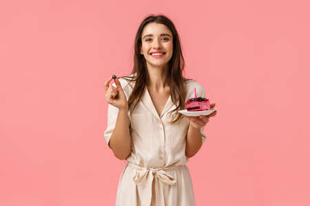 Birthday girl eating delicious cake, blowing-out candle and smiling joyfully, holding blueberry, having party celebrating b-day with friends, grinning standing in dress over pink background