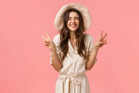 Happiness, cheer and joy concept. Silly good-looking tender, feminine girlfriend in hat and dress, showing peace signs and laughing carefree, enjoying vacation, being on trip, pink background