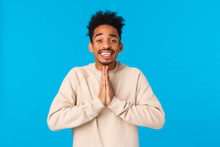 Pretty please I need your help. Charismatic cute and silly african-american young guy begging lend car, press palms together in pray, supplication gesture, smiling as pleading over blue background