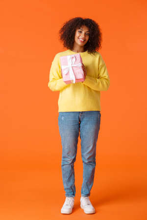 Full-length vertical shot cute and friendly african-american girl prepared gift for girlfriend, standing with wrapped present smiling tenderly camera, want congratulate with valentines day Stock Photo