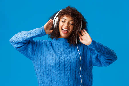 Waist-up portrait carefree happy smiling woman relaxing, singing along, playing karaoke app in earphones, close eyes passiontly lip-sync to music in headphones, standing blue background Stock Photo