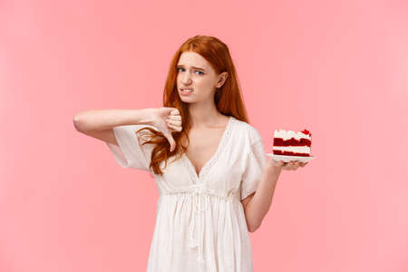 Never buy at this store again. Displeased and disappointed picky cute redhead girl frowning, grimacing from dislike, showing thumb-down in disapproval as tried awful, disgusting cake 版權商用圖片