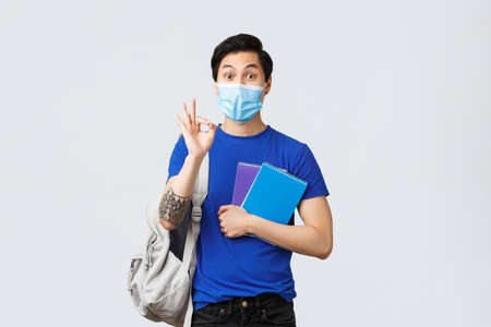 Back to school, studying during covid-19, education and university life concept. All good under control. Handsome asian male student in medical mask assure no problem with okay sign, head to class