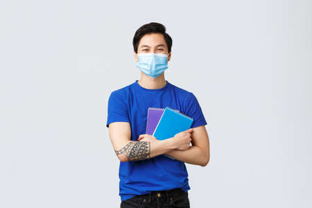 Back to school, studying during covid-19, education and university life concept. Happy young male student in medical mask, holding notebooks, homework and smiling, stand grey background Imagens