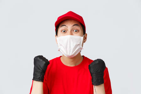 Covid-19, self-quarantine online shopping concept. Hopeful and relieved delivery guy in red cap, medical mask and gloves, fist pump achieve goal, stare amazed, received raise in courier service