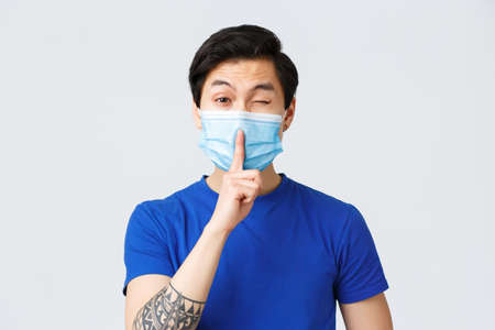 Different emotions, lifestyle and leisure during coronavirus, covid-19 concept. Cheeky handsome asian man in medical mask promise keep secret, shush and wink coquettish, be silent