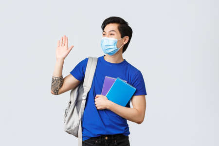 Back to school, studying during covid-19, education and university life concept. Carefree smiling male student waving hand at friend college, head campus or lecture, wear backpack and medical mask Imagens