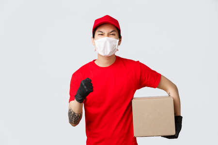 Deliver your goods no matter what. Confident asian delivery guy in red uniform cap and t-shirt, raise hand encourage place your order, holding box pachage, wear medical mask and gloves Banco de Imagens