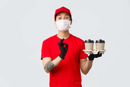 Your order is safe with our couriers. Charismatic delivery guy in red uniform and medical mask, gloves, holding drinks, bring order to client doorstep, contactless delivery, show okay, delicious sign Standard-Bild