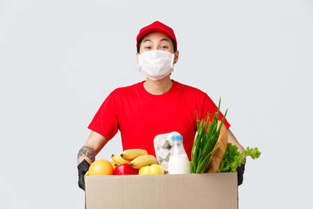 Online shopping, food delivery and coronavirus pandemic concept. Smiling delivery man in red uniform, holding box with fresh groceries, wear medical mask and gloves, contactless shopping