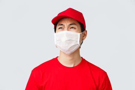 Covid-19, self-quarantine online shopping and delivery concept. Complaining reluctant courier in red t-shirt and cap, medical mask, whining about night shifts at work, look disappointed