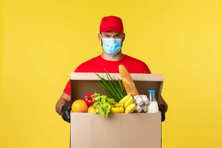 Takeaway delivery, covid-19 quarantine and groceries concept. Serious grumpy courier in medical mask and red uniform, bring customer food box order, standing yellow background