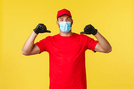 Express delivery during pandemic, covid-19, safe shipping, online shopping concept. Surprised courier in red uniform, medical mask and gloves, pointing himself and look amazed