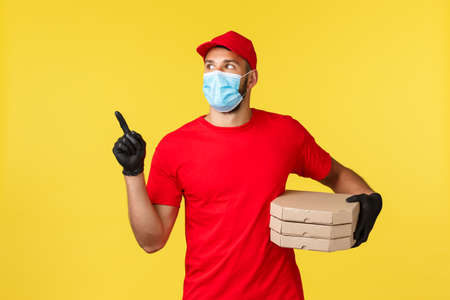 Food delivery, tracking orders, covid-19 and self-quarantine concept. Young courier searching house to deliver pizza to client, look left, wear red uniform and protective personal equipment Foto de archivo