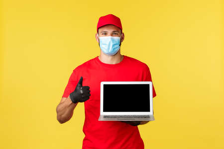covid-19, safe shopping, express delivery and order tracking concept. Friendly young courier in red uniform and medical mask, show thumb-up, recommend visit link or site, show laptop screen
