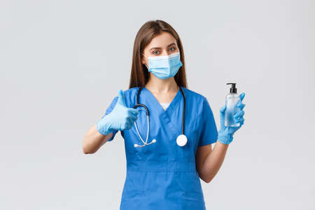 Covid-19, preventing virus, healthcare workers and quarantine concept. Confident female nurse or doctor in blue scrubs, medical mask protective equipment, thumb-up recommend use hand sanitizer