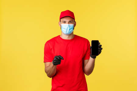 Food delivery, tracking orders, covid-19 and self-quarantine concept. Young cheerful courier in medical mask and gloves, red uniform, show smartphone app, screen phone and pointing camera 写真素材
