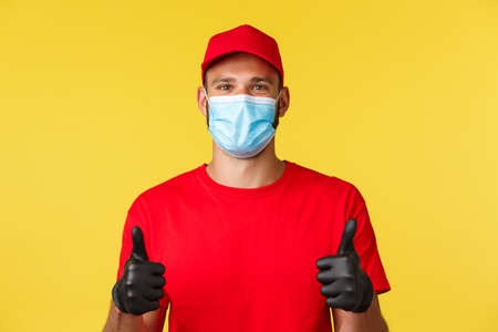 Covid-19, delivery orders, shopping, contactless payment and social distancing concept. Cheerful and supportive courier in red uniform cap and t-shirt, medical mask gloves, show thumbs-up