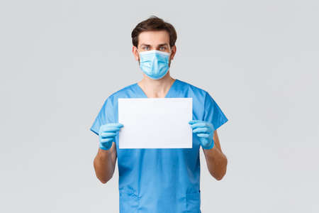 Covid-19, quarantine, hospitals and healthcare workers concept. Serious young doctor in medical mask, scrubs and gloves, holding paper with manifest or sign, fighting coronavirus, asking stay home Archivio Fotografico