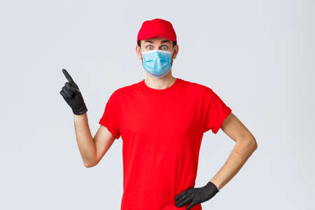 Covid-19, self-quarantine, online shopping and shipping concept. Surprised delivery guy popping eyes amazed or excited as showing promo, pointing finger left, wear courier uniform and medical mask Foto de archivo