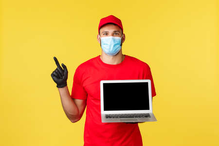 covid-19, safe shopping, express delivery and order tracking concept. Excited young courier in medical mask and red uniform, pointing finger left at promo, showing laptop screen, link or webpage