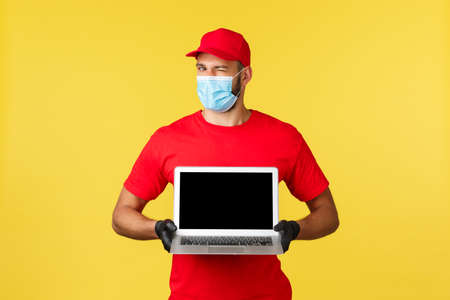 covid-19, safe shopping, express delivery and order tracking concept. Handsome courier in red uniform, medical mask and gloves, wink camera and showing page site on laptop screen
