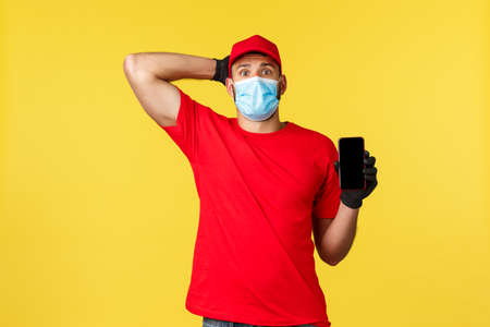 Food delivery, tracking orders, covid-19 and self-quarantine concept. Worried and confused young courier in medical mask and gloves, scratch head nervous, showing smartphone display
