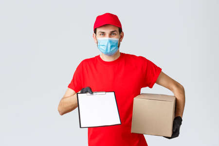 Packages and parcels delivery, covid-19 quarantine delivery, transfer orders. Friendly courier in red uniform, face mask and gloves, holding package box and give clipboard order sign form to client