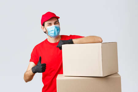 Packages and parcels delivery, covid-19 quarantine and transfer orders. Confident courier in red uniform, gloves and medical mask, encourage call service, show thumb-up lean on boxes