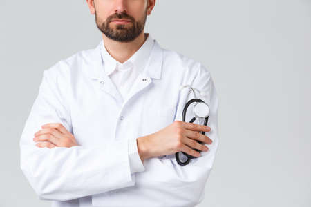 Hospital, healthcare workers, covid-19 treatment concept. Cropped shot of serious-looking confident doctor with beard, wearing white scrubs. Physician cross arms chest, holding stethoscope