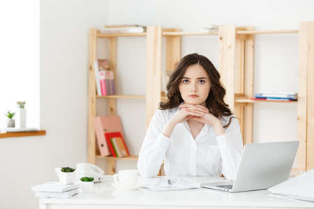 Young attractive woman at a modern office desk, working with laptop and thinking about something. Archivio Fotografico