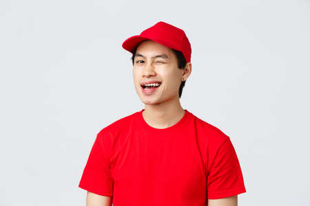 Delivery, contactless orders and shopping concept. Enthusiastic asian courier in red uniform t-shirt and cap, smiling amused and wink to client, recommend service, standing grey background
