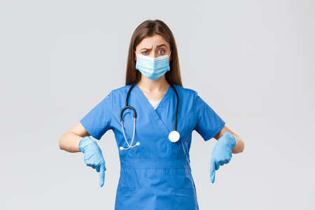 Covid-19, preventing virus, health, healthcare workers and quarantine concept. Skeptical and unsure female nurse or doctor in blue scrubs, personal protective equipment, pointing fingers down unsure