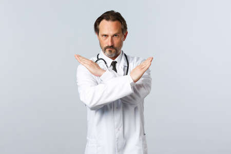 Covid-19, coronavirus outbreak, healthcare workers and pandemic concept. Serious displeased male doctor in white coat, cross hands to show stop gesture, prohibit or forbid smth