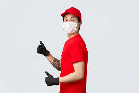 Wow very fast delivery. Excited asian delivery guy in red cap and t-shirt, wear protective medical mask, gloves, turn to camera with thumbs-up, recommend courier service, online shopping concept