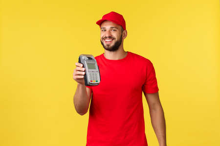 Contactless payment, online delivery, internet shopping and parcel tracking concept. Friendly smiling, bearded employee giving customer POS terminal to pay for order, standing yellow background 写真素材