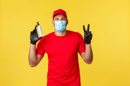 Covid-19, delivery orders, shopping, contactless handling and social distancing concept. Friendly courier in red uniform, gloves and medical mask, show peace sign adn recommend hand sanitizer